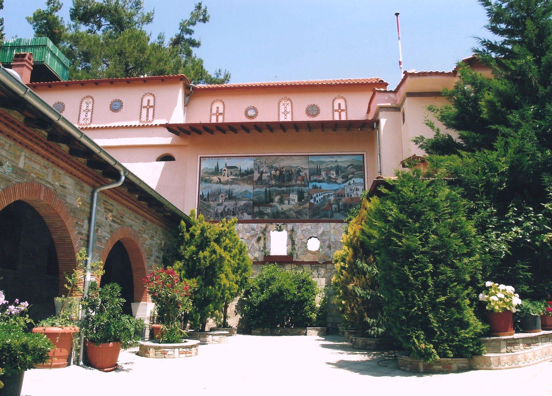 Δεξιά πλευρά του Ναού της Αγίας Παρασκευής (Καθολικό) και η πίσω πλευρά του Ξενώνα, όπου διακρίνεται η παράσταση με το Ιστορικό της Μονής, έργο του Αγιογράφου Ράιδου.